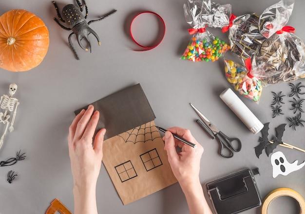 Emballage étape par étape d'un cadeau pour halloween, dessinez une toile d'araignée sur la maison avec un feutre