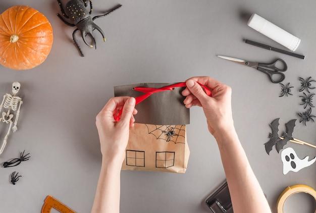 Emballage étape par étape d'un cadeau pour halloween, pose à plat. attacher le ruban avec un arc