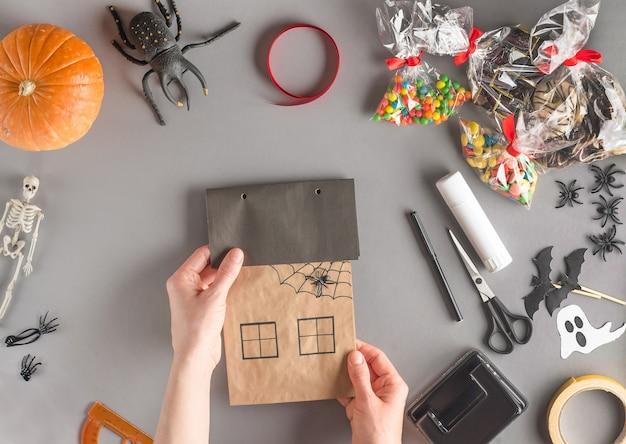 Emballage étape par étape d'un cadeau pour halloween, pose à plat, percez des trous pour le ruban adhésif sur le toit de la maison