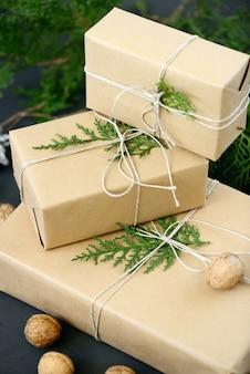 Emballage de paquets de noël écologiques avec papier brun, ficelle et branches de sapin naturel sur fond sombre