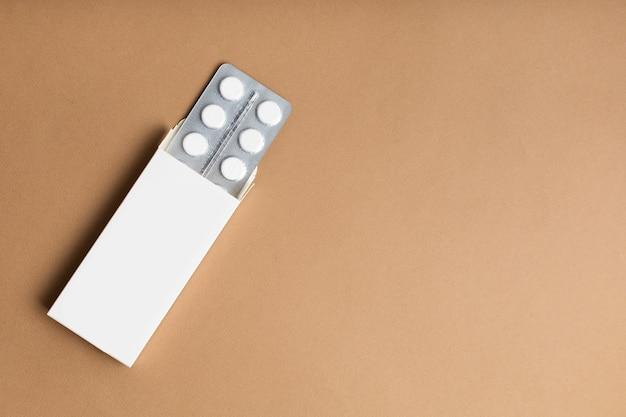 Emballage de pilules blanches sur fond coloré