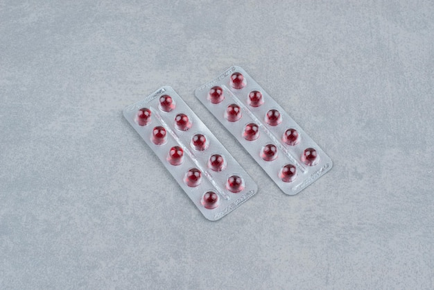 Emballage de pilules de médecine rouge ovale sur fond gris