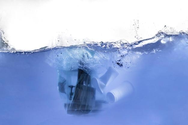 L'emballage en plastique contenant des déchets à l'intérieur flotte dans la ligne sous-marine de l'eau de mer, problème d'environnement de décharge