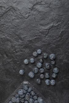 Emballage en plastique de délicieux bleuets frais sur une surface noire