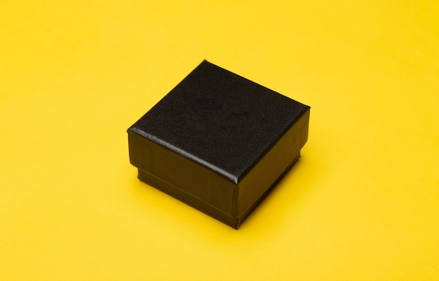 Emballage de produit mini boîte noire isolé sur mur jaune