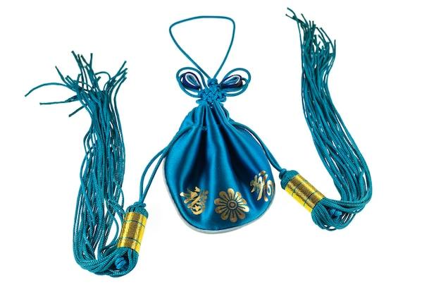Emballage de sac à cordon vert style chinois sur surface blanche