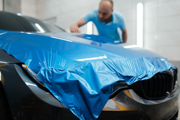 Emballage de voiture, l'homme installe une feuille de vinyle ou un film protecteur sur le capot. le travailleur fait des détails automatiques