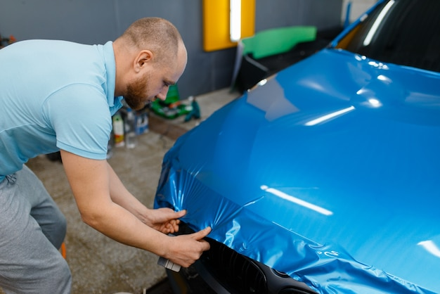 Emballage de voiture, l'homme avec raclette installe une feuille de vinyle ou un film protecteur sur le capot. le travailleur fait des détails automatiques