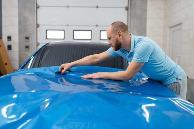 L'emballage de voiture mâle installe une feuille ou un film de protection en vinyle sur le capot du véhicule. le travailleur fait des détails automatiques