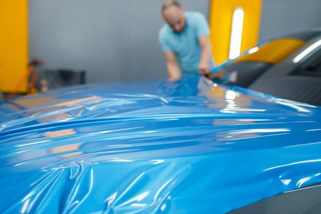L'emballage de voiture masculin met une feuille de vinyle ou un film protecteur sur le capot. le travailleur fait des détails automatiques