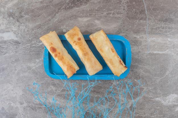 Emballages de crêpes sur un plateau bleu sur une surface en marbre