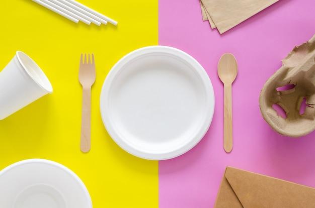 Emballages jetables, compostables et recyclés sur fond jaune et rose