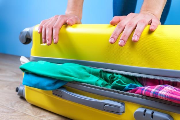 Emballer les vêtements dans une valise jaune. emballez les articles nécessaires pour un voyage ou un voyage d'affaires. vacances, vacances. concept de voyage