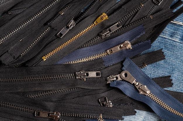 Emballez beaucoup de rayures de fermetures à glissière antiques en laiton bleu marine en métal avec motif de curseurs pour la couture à la main couture maroquinerie sur le fond en bois bleu