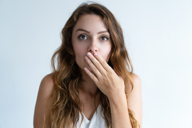 Embarrassé jolie jeune femme couvrant la bouche avec la main