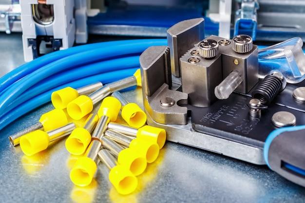 Embouts isolés à l'extrémité du cordon jaune inutilisés avec dénudeur de fil et fil toronné bleu posé sur une plaque de montage en métal