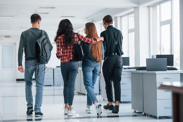 Embracings amicaux. groupe de jeunes marchant dans le bureau à leur pause