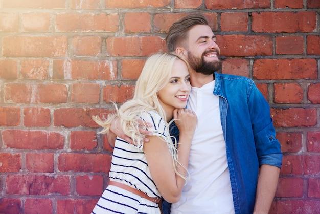 Embrassant le couple debout devant le mur de briques