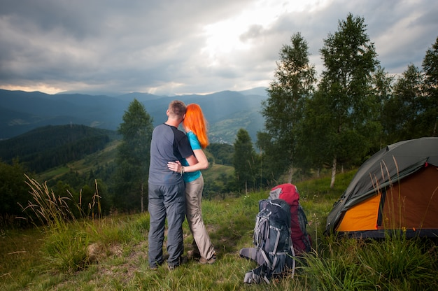 Embrassant un couple debout près du camping et regardant au loin dans les montagnes, les forêts et frappant les rayons du soleil à travers un ciel nuageux au coucher du soleil