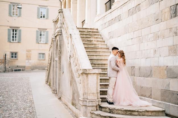 Embrassant les jeunes mariés debout sur les marches d'un ancien bâtiment à bergame, italie