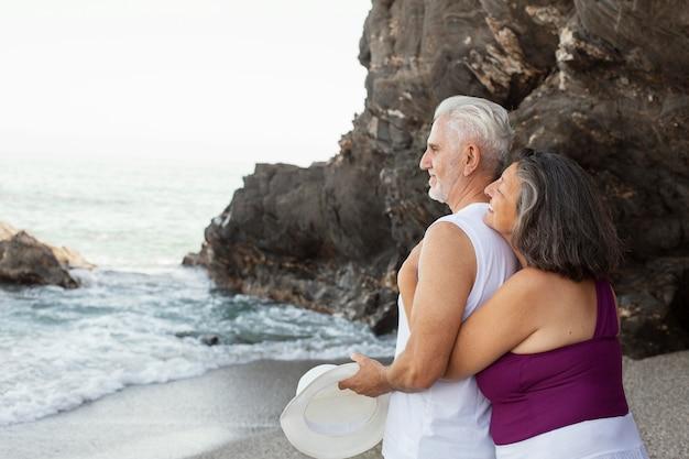 Embrassé un couple de personnes âgées profitant de leur journée à la plage