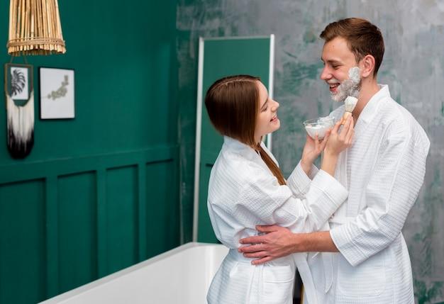 Embrassé smiley couple portant des peignoirs avec de la mousse à raser