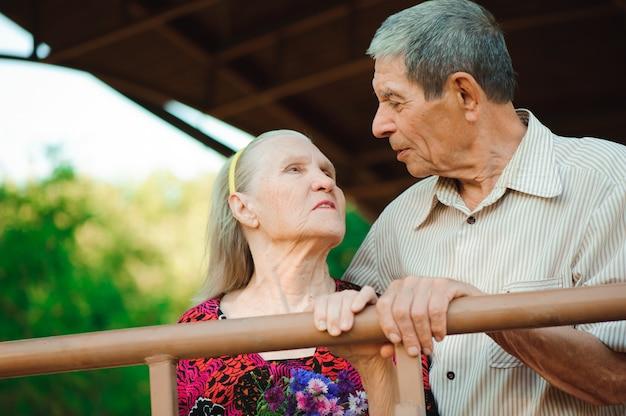 Embrasser et baiser du vieux couple dans un parc par une journée ensoleillée.