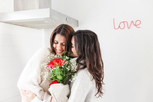 Embrasser des copines heureuse avec bouquet