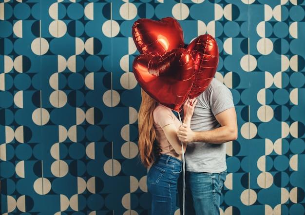 Embrasser un couple caucasien se cache derrière des ballons aiguisés en forme de coeur d'air sur un mur bleu