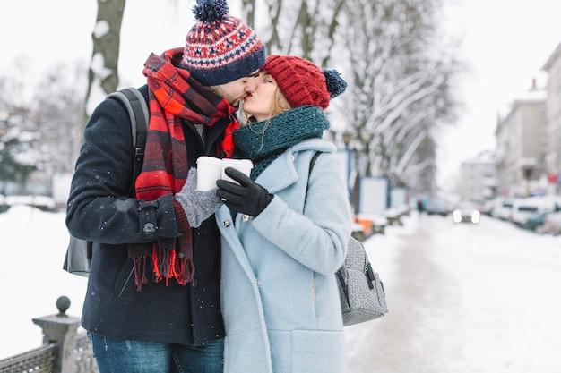 Embrasser un couple élégant sur une rue enneigée