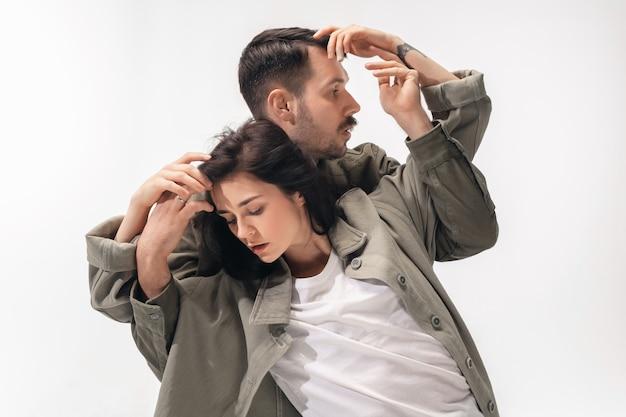Embrasser. couple à la mode à la mode isolé sur le mur du studio blanc.