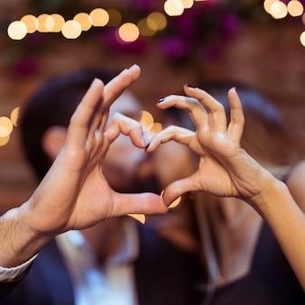 Embrasser couple montrant le symbole du coeur