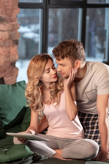 Embrasser l'homme. petite amie aimante embrassant son homme assis au lit ensemble et portant un pyjama confortable