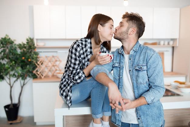 Embrasser jeune homme et femme heureux dans la cuisine, petit-déjeuner, couple ensemble le matin, souriant, prendre le thé
