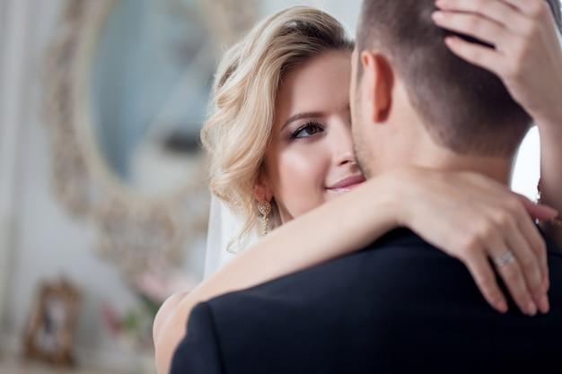 Embrasser le jour du mariage. belle mariée embrassant marié dans le cou