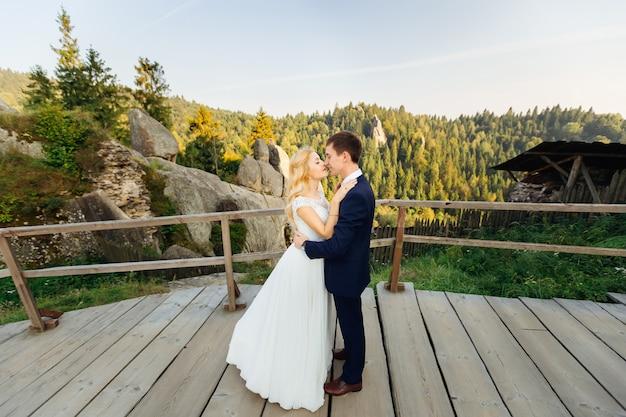 Embrasser tendrement couple contre les rochers et la forêt d'automne lointaine