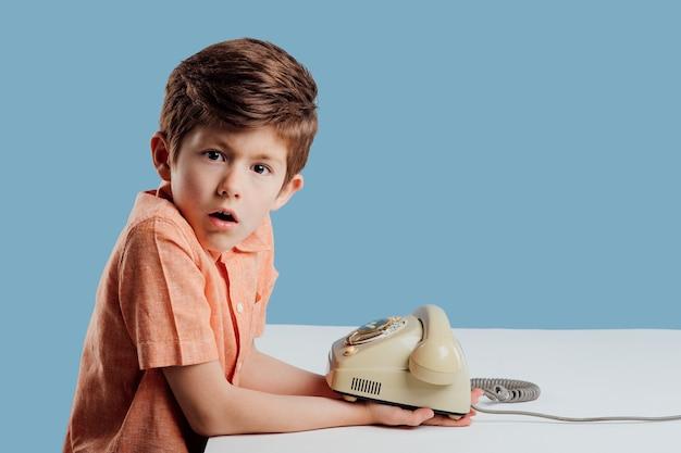 Émerveillement petit garçon avec un vieux téléphone regarde la caméra assis à la table fond bleu