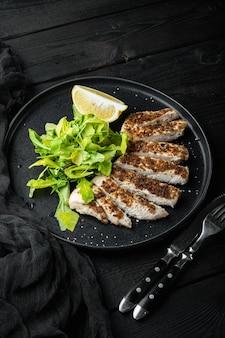 Émietté, filet de poitrine de poulet grillé, sur table en bois noir