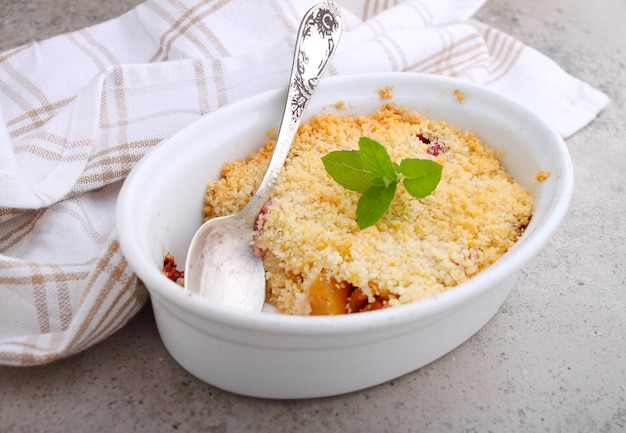 Émietter avec des fraises et des pommes sur une plaque blanche et une table en béton.