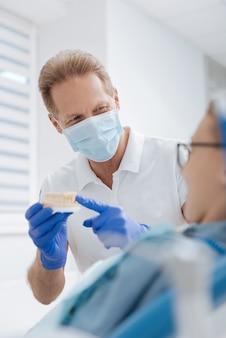 Éminent médecin amical formé s'assurant que son patient comprend la procédure qu'elle subit et n'a pas peur