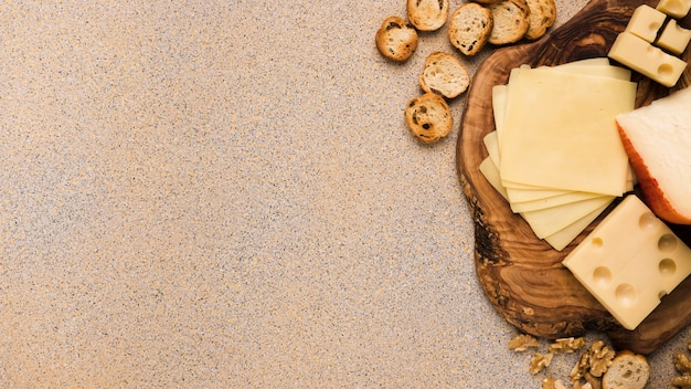 Emmental et gouda avec des tranches sur un dessous de verre avec des tranches de pain et des noix sur un fond texturé beige