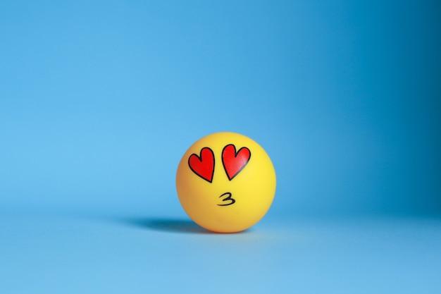 Émoticône d'amour avec la bouche s'embrasser isolé sur fond bleu