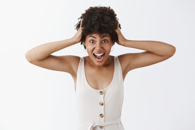 Émotif charmant afro-américain en détresse en salopette blanche tirant les cheveux de la tête en criant grimaçant et en faisant une expression inquiète, debout énervé sur un mur gris