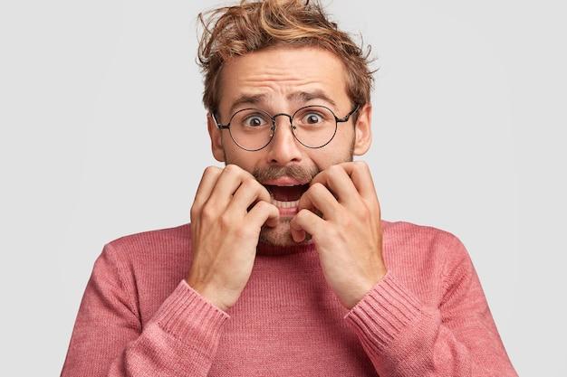 Émotif déprimé jeune homme embarrassé mord les ongles dans la panique, regarde avec une expression nerveuse