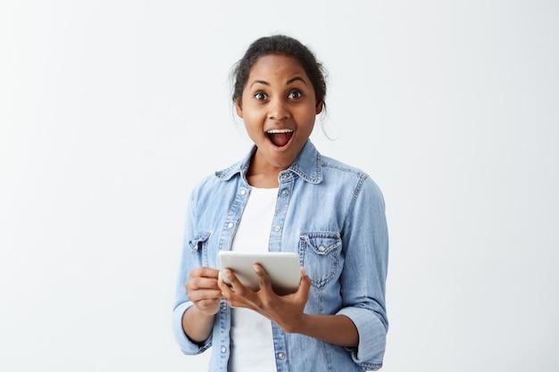 Émotionnel étonné jeune femme à la peau sombre en chemise bleue tenant dans sa tablette mains, surpris et choqué par des nouvelles positives inattendues. expressions et émotions du visage humain