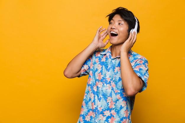 Émotionnel excité jeune homme asiatique debout isolé sur un espace jaune, écouter de la musique avec des écouteurs.
