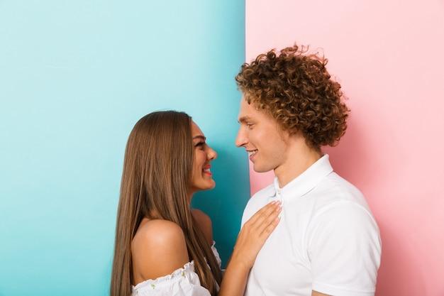 Émotionnel jeune couple d'amoureux heureux étreignant posant isolé.