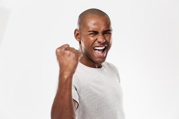 Émotionnel jeune homme africain debout isolé faire geste gagnant