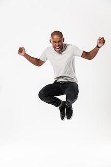 Émotionnel jeune homme africain sautant