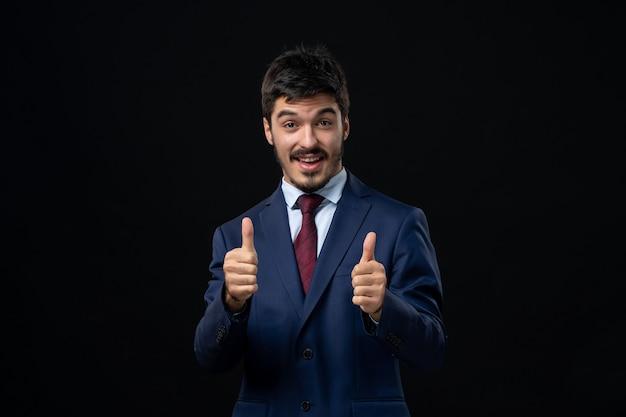 Émotionnel et jeune homme barbu faisant un geste correct avec les deux mains sur un mur sombre isolé